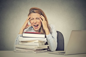 Too much work tired stressed young woman sitting at her desk with books in front laptop computer isolated grey wall office background. Busy college schedule burnout workplace sleep deprivation concept